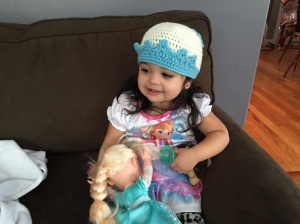 Doodlebug in her Elsa nightgown, with her Elsa knit cap and her Elsa doll, probably watching ... well, Elsa.